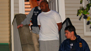 Kareem Burke led out of home by federal agents.
