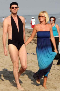 A swim-suited Jim Carrey strolls on the beach with girlfriend, Jenny McCarthy